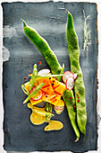 Food art: green beans with persimmon, radishes and mustard sauce