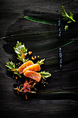 Food art: salmon with caviar, celery, roasted onions and sesame seeds on a black painted surface