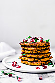 Sweet potato latkes, stacked, with yogurt, herbs, and pomegranate