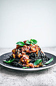 Black bean spaghetti with tomato sauce, basil, and vegan cheese