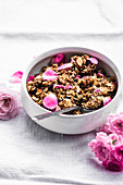 Almond and rose granola in handmade bowl on linen