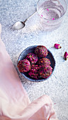 Healthy truffle candies made of dates, cocoa and cashew and covered with rose petals