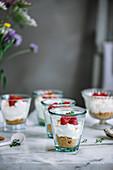 Dessert mit Keksboden, Mascarponecreme und Himbeeren in Gläsern serviert