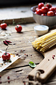 Spaghetti, tomatoes and hot pepper on wooden rustic table