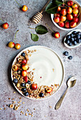 Yogurt and fresh summer fruit on grey background
