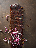 A long rack of ribs sauced with red onion spread over it and spices scattered around thes surface