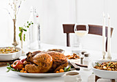 A beautiful, roast chicken holiday dinner on a clean white table with clean, yet rustic, settings