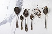 Variety of different black peppers allspice, pimento, long pepper, monks pepper, peppercorns and ground powder in vintage spoons over white marble texture background