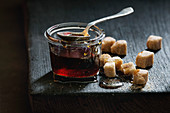 Homemade liquid transparent brown sugar caramel in glass jar standing on black wooden board with spoon and can sugar cubes