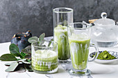 Matcha green tea iced latte or cocktail in three different glasses with ice cubes, matcha powder and jug of milk on white marble table