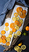 Candied orange, lemon and lime slices with a knife on a wooden cutting board