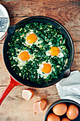 Spinach with eggs served in an iron pan