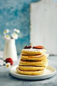 Ein Stapel Mandeldrink-Pancakes mit Erdbeeren und Puderzucker