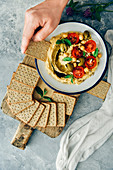 A woman dipping a cracker into a bowl of hummus without tahini topped with cherry tomatoes and green olives