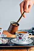 A woman pouring Turkish coffee into a Turkish coffee cup from a copper Turkish coffee pot