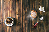 Homemade croissant with sugar powder, cup of coffee, jug of milk, vintage sieve over wooden plank background