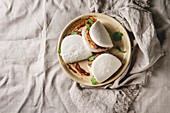 Asian sandwich steamed gua bao buns with pork belly, greens and vegetables served in ceramic plate over linen tablecloth