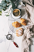 Homemade croissant with sugar powder on cooling rack, Breakfast with cup of coffee, jug of milk