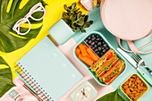 Creative flat lay with healthy lunch and office or school supplies on pastel colors background
