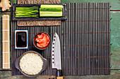 Zutaten und Utensilien für Sushi auf Bambusmatte (Japan)