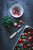 Stillleben mit Thymian und frischen Erdbeeren in Kiste und Schälchen (Aufsicht)