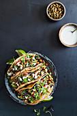 Tacos mit Gemüsefüllung in Schale auf blauem Untergrund (Aufsicht)