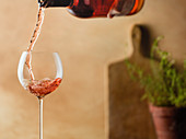 Rose being poured into delicate wine glass in a warm, tuscan kitchen setting