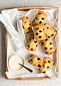 Individual blueberry loaf cakes with a bowl of cream on a wooden tray