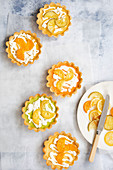 Five lemon, lime and orange tarts with a plate of candied citrus fruit slices