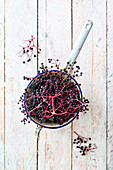 Elderberries in an enamel sieve