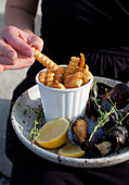 A woman holding a plate of french fries and mussels in a thyme, lemon, white wine and garlic sauce