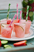 Gin and tonic popsicles with strawberries and cucumbers on a mint coloured tray