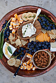 A copper tray on a stone surface, with marbled cheddar cheese cubes, concord grapes, blueberries, crackers, brie topped with honey and sage, artichoke dip with thyme, almonds and a sprig of sage