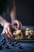 Vegan blueberry scones on baking rack with dark background
