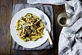 Pasta with zucchini and summer squash on wooden table
