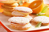Orange cookies filled with jam and dusted with powdered sugar