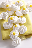 Delicate meringue shapes with yellow sugar decorations