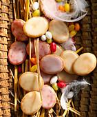 Zitronen- und Himbeerplätzchen mit Glasur in geflochtenem Korb mit Federn zu Ostern