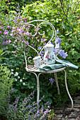 Kaffeekanne und Tassen auf Stuhl neben Akelei und Glockenblume