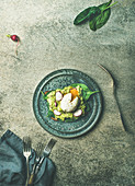 Wholegrain toasts with avocado, spinach and poached egg on plate over grey concrete background