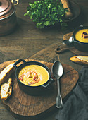 Corn creamy soup with shrimps served in individual pots with bread over rustic dinner table