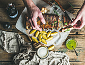 Man eating roasted pork ribs with garlic, rosemary, fried potato and green herb sauce