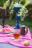 Glass of tea, melon slices and painted goblet on table in garden