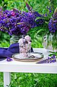 Brombeereis im Glas zwischen blauen Blüten