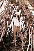 Dunkelhaarige Frau mit Hut in weißer Hemdbluse und Hose vor gesammelten Ästen für Lagerfeuer