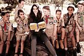 Dunkelhaarige Frau mit Schulkindern in Uniform beim Vorlesen