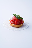 A mini tartlet with strawberries against a white background