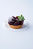 A mini tartlet with cherries against a white background
