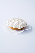 A mini tartlet with rhubarb and meringue on a white background