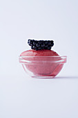 Blackberry sorbet in a glass bowl against a white background
